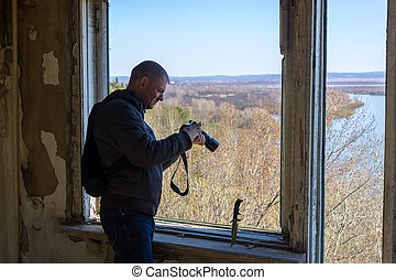 A man holds a camera at the window inside an abandoned building