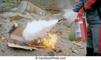 A man holds a fire extinguisher in his hands and...