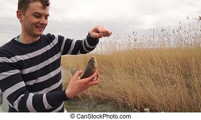 a man holds a fish caught on a fishing rod. fisherman. men's hobbies and outdoor recreation.