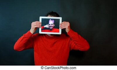 A man holds a tablet instead of a face. On the screen, the man in the crown makes dance moves.