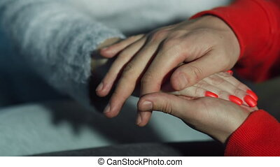 Man holds a woman's hand, close-up, caring for a loved one