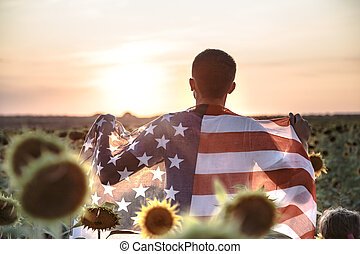 a man holds an American flag at sunset.