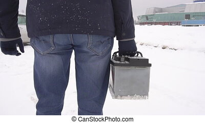 A man holds in his hand a car battery in the winter against...