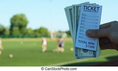 A man holds in his hand a ticket bookmaker's office and money dollars against the background of the stadium where they play football, sports betting