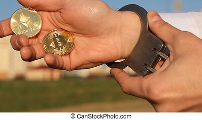 A man holds in his hand bitcoin and etherium, handcuffs,...