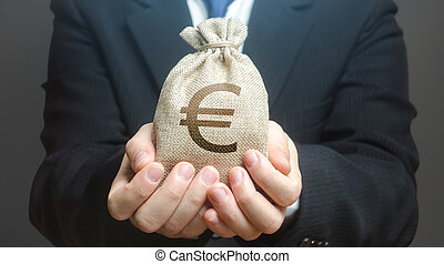 A man holds out a euro money bag. Granting financing business project or education. Provision cash financial loan credit. Investment. Bank deposit. Budget management, tax collection. Trade, economics.