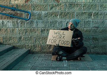 A man, homeless, a man asks for alms on the street with a sign will work for food. Concept of homeless person, addict, poverty, despair.