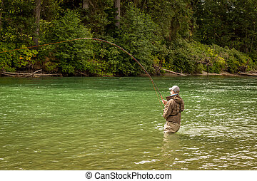 A man hooked into a fish while fly fishing on a deep green river.