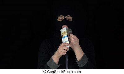 A man in a balaclava mask is standing with a bundle of rubles. The thug leafing through the money and rejoices. On a black background.
