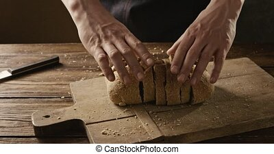 A man in a black apron takes sliced fresh bread on a wooden...