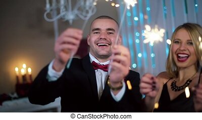 a Man in a Black Suit and a Woman in Evening Black dress waving sparklers, in a white room with fireplace and Christmas tree