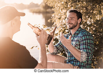 A man in a blue shirt sits on the river bank with a bottle of beer and tells something to the old man
