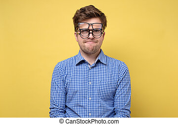 A man in a blue shirt with several glasses for vision feeling sad. H