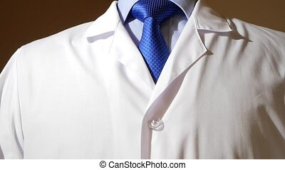 a man in a business suit and tie is putting on a white robe....