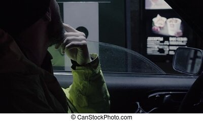 A man in a car looking at auto fast food menu