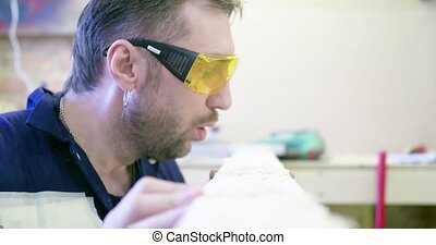 A man in a carpentry workshop wearing protective glasses...