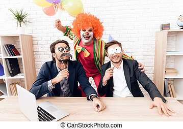 A man in a clown suit is standing next to other men in a bright business office on Fools' Day.