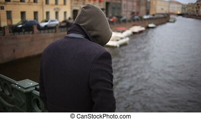 man in a coat stands on a bridge and looks down at the black...