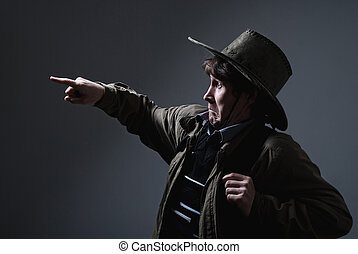A man in a cowboy hat fright shows a finger in the direction of