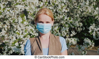 A man in a gauze bandage against a background of flowering...
