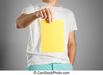 A man in a gray t-shirt holding blank clear yellow of the sheet. Closeup. Isolated