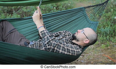 A man in a hammock making selfie on tablet. Man in the woods with a beard and glasses