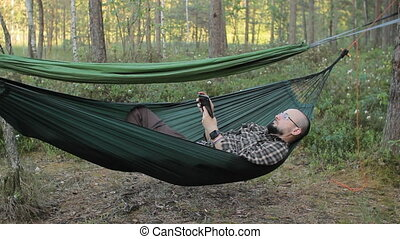 A man in a hammock touch tablet. Man in the woods with a beard and glasses