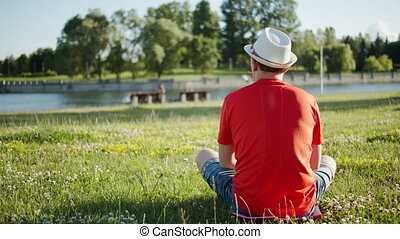 A man in a hat sits in nature on a sunny day, rear view, summertime