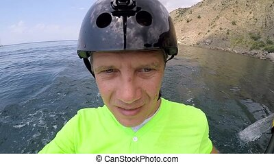A man in a helmet sailed on a kayak in the sea - A man is...
