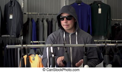 A man in a hood and glasses steals a T-shirt from a store. ...