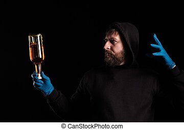a man in a hood holds a bottle of alcohol in his hand, the other hand is free