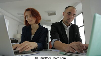 a man in a jacket sits in a large bright spacious office with a woman and tells the latest news of the day.