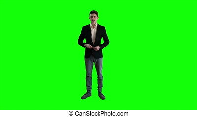 A man in a jacket standing at background of a green screen.