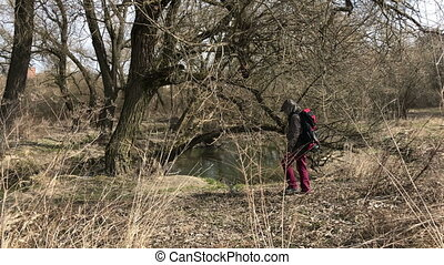 A man in a jacket with a hood on is walking along the river...