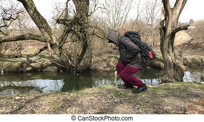 A man in a jacket with a hood on is walking along the river bank. Raises the glass bottle, throws it to the side, and goes on. Spring landscape.