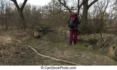 A man in a jacket with a hood on is walking in a spring...