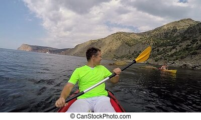 A man in a kayak in the sea - A group of people makes an...
