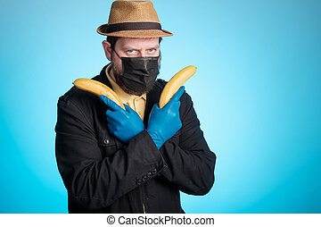 a man in a mask and a hat holds bananas in his hands like pistols