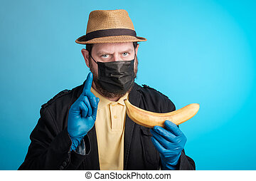a man in a mask and gloves holds a banana in his hand