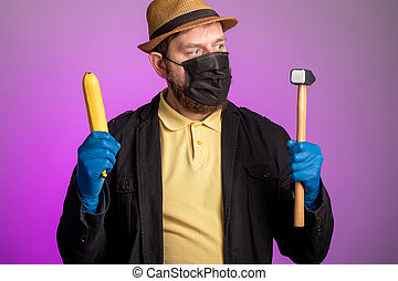 a man in a mask and hat holds a banana in one hand and a hammer in the other