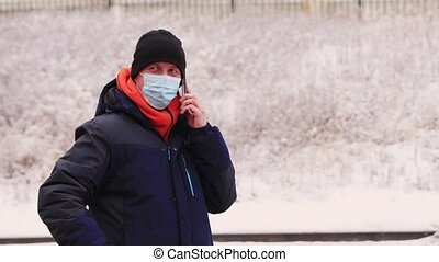 A man in a mask is emotionally talking on the phone and gesturing with his hand