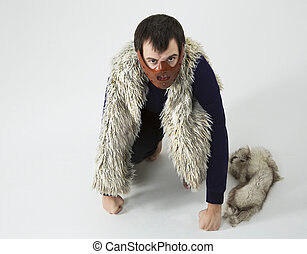 a man in a mask on his face. in vest, with fur