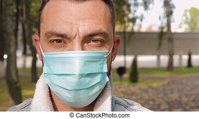 A man in a medical mask looks at the camera close-up.