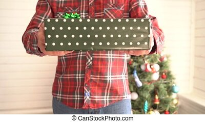 A man in a plaid shirt gives a Christmas present.