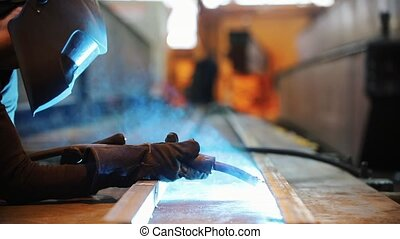 A man in a protective mask performs welding work.