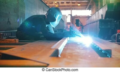 A man in a protective mask welds channel