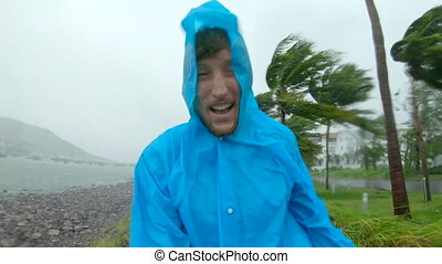 A man in a raincoat is under a hevy rain and stormy wind. Shot on an action camera. Tropical storm concept. Contains natural sound.