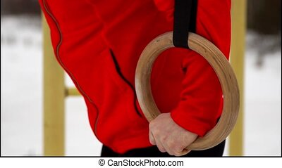 A man in a red jacket doing gymnastics Stationary Rings in...