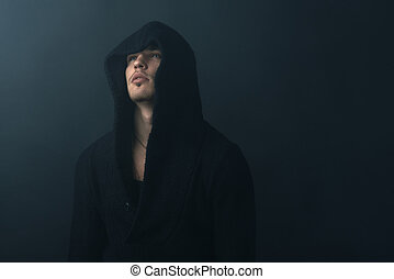 man in a robe quietly looking into the light - a man in a...