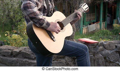 A man in a shirt and jeans playing the guitar